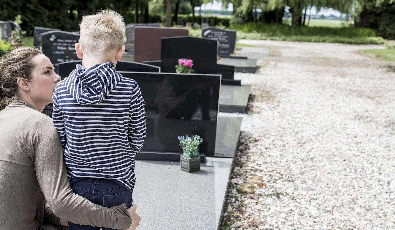 Sorgerechtsverfügung: Kind und Mutter stehen vor dem Grab des Vaters.