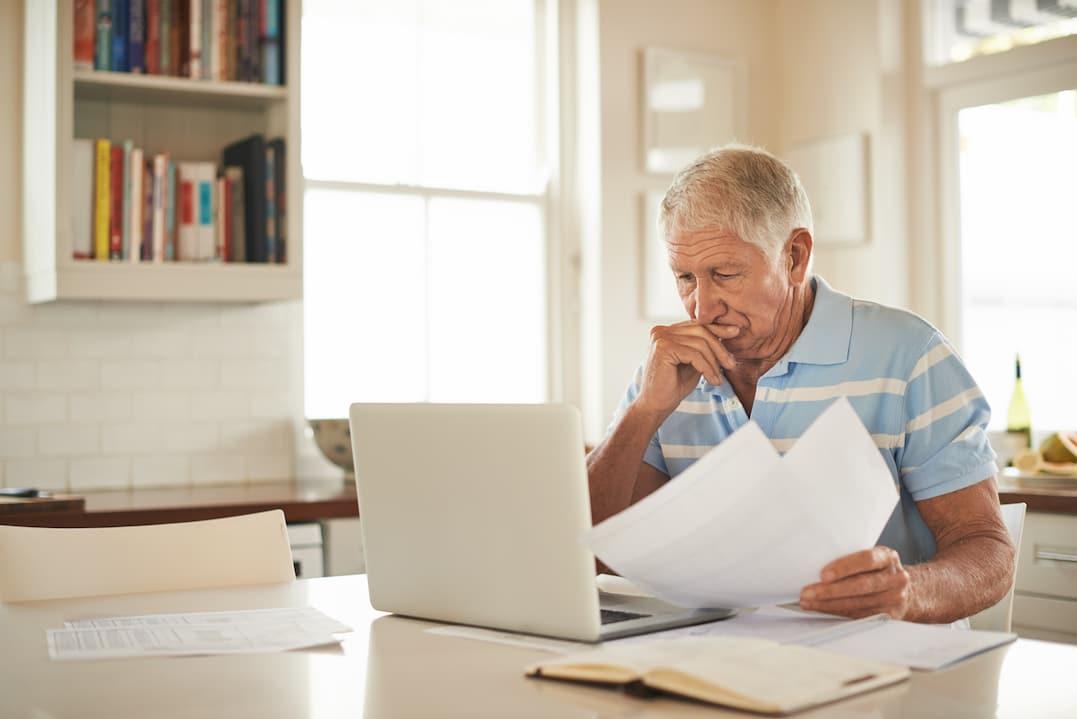 Veträge Kündigen: Ein Mann sitzt vor dem Computer zu Hause.