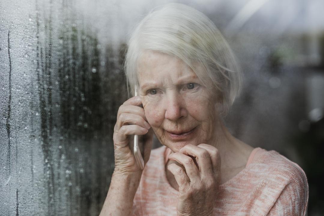 Frau hält Telefon am Ohr und steht vor dem Fenster.