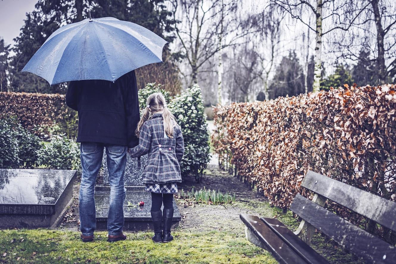 Papa und Tochter stehen vor einem Grab.
