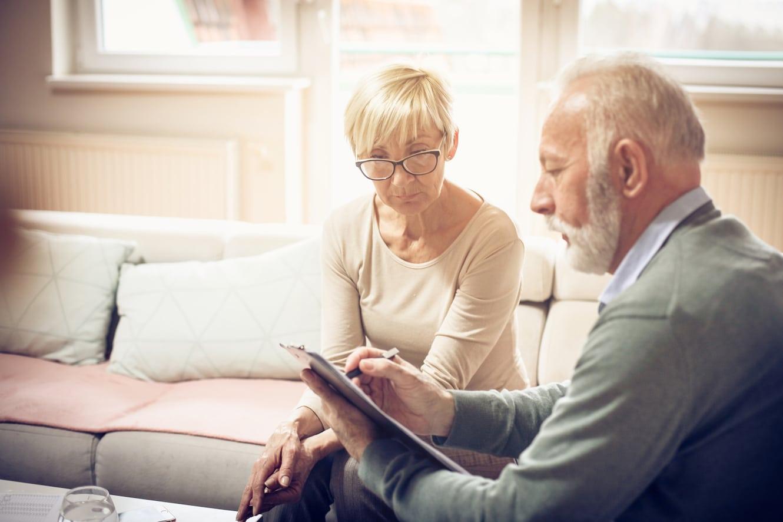 Zwei ältere Personen sitzen auf dem Sofa und schauen sich etwas auf dem iPad an.
