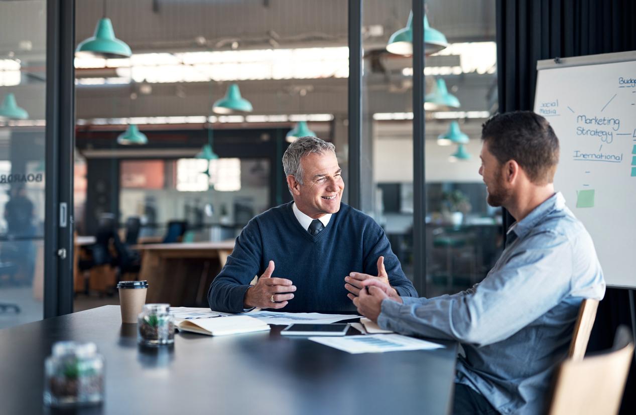 Vater und Sohn sitzen am Tisch in einem Meeting-Raum. Sie planen die Unternehmensnachefolge.