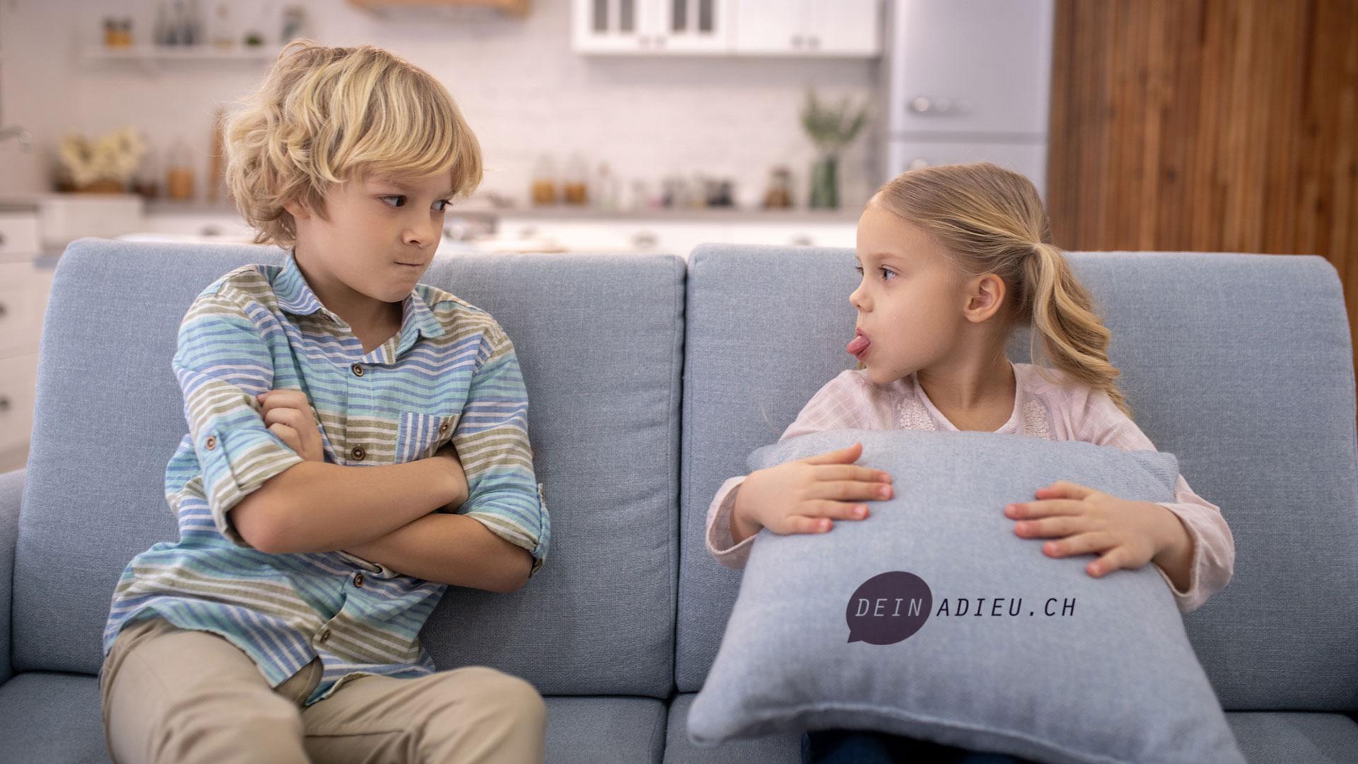 zwei Geschwister sitzen auf dem Sofa und schenken sich böse Blicke.